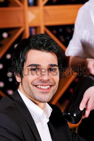 Waitress in restaurant offering red wine Stock photo © Kzenon