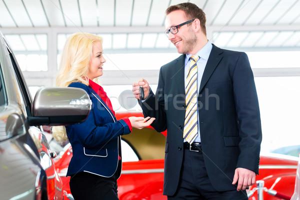 Woman with key to new auto in car dealership Stock photo © Kzenon