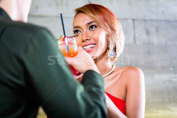 Asian couple drinking cocktails in fancy bar Stock photo © Kzenon
