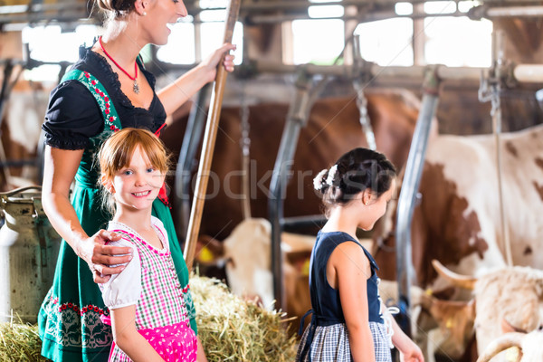 Bavarian mother showing children cows in cowhouse Stock photo © Kzenon