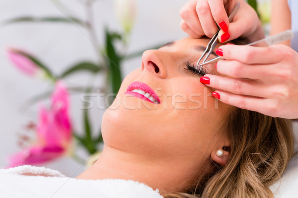 Woman receiving false eye lashes in beauty studio Stock photo © Kzenon