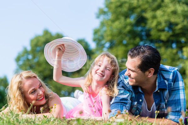 Girl with Mum and Dad, swaying her hat Stock photo © Kzenon