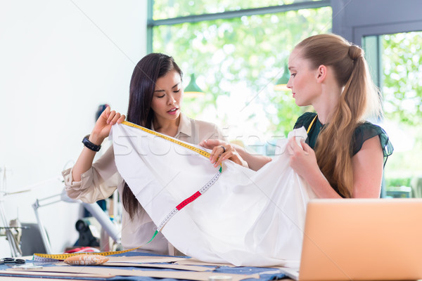 Young Fashion designer women measuring cloth  Stock photo © Kzenon