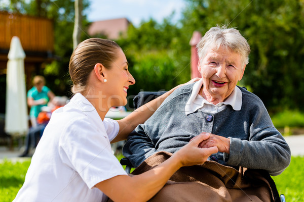 Nurse holding hands with senior woman in wheelchair Stock photo © Kzenon