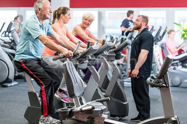 Group spinning with personal trainer in gym Stock photo © Kzenon
