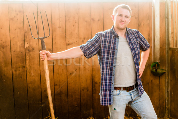 Man clearing stable with pitchfork Stock photo © Kzenon