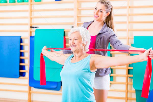 Senior woman with stretch band at fitness Stock photo © Kzenon