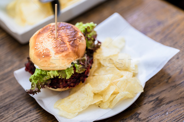 Close-up of burger with green salad and potato chips Stock photo © Kzenon