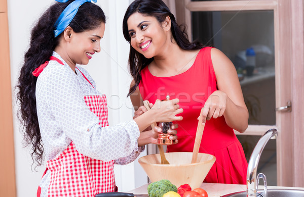 Two female friends preparing together vegetarian salad  Stock photo © Kzenon