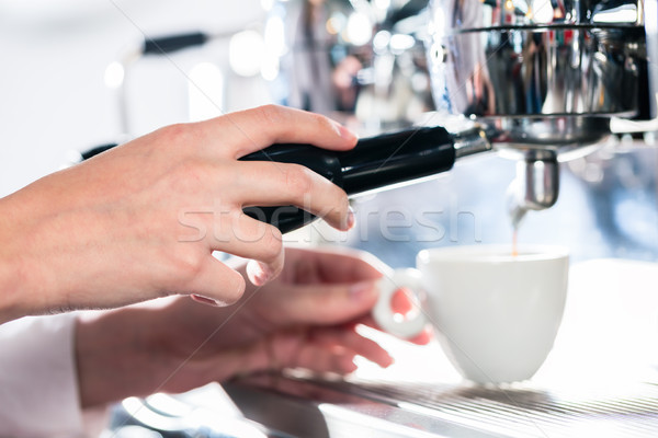 Close-up of female hand on the portafilter of an automatic coffe Stock photo © Kzenon
