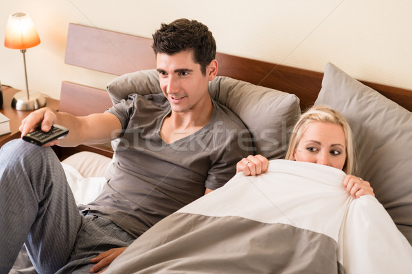 Couple sitting in bed while watching TV Stock photo © Kzenon