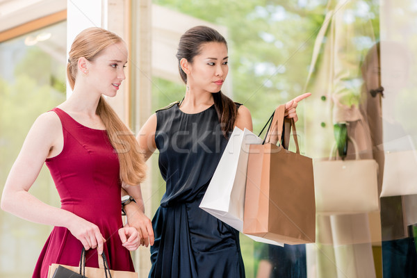 Two female best friends looking at the latest fashion trends Stock photo © Kzenon