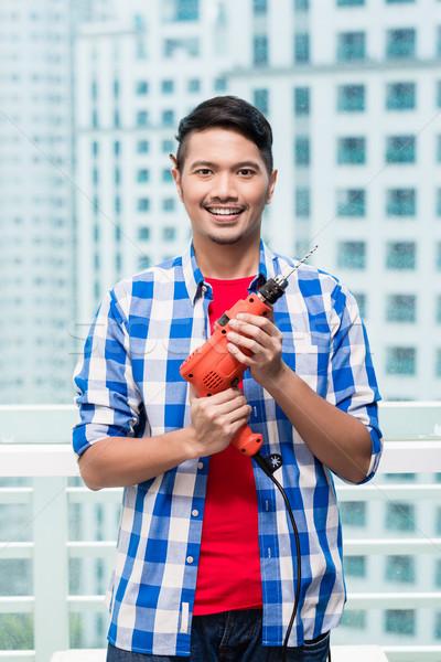 Fiatal indonéz férfi erő fúró kész Stock fotó © Kzenon