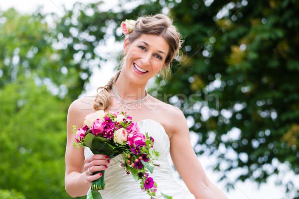Bride in wedding dress with bridal bouquet Stock photo © Kzenon