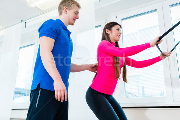 Woman in gym getting instructions for using sports equipment Stock photo © Kzenon