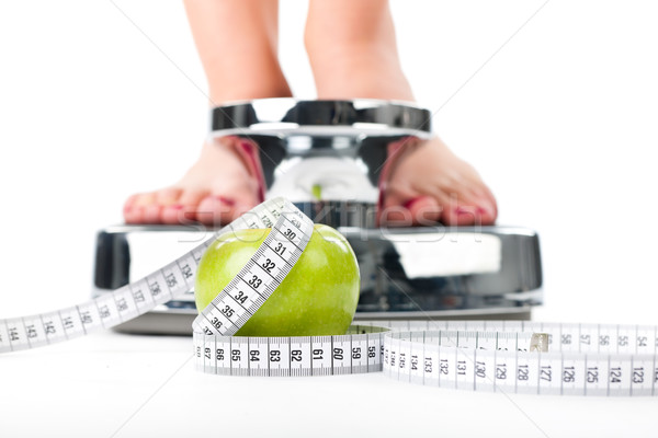 Young woman standing on a scale Stock photo © Kzenon