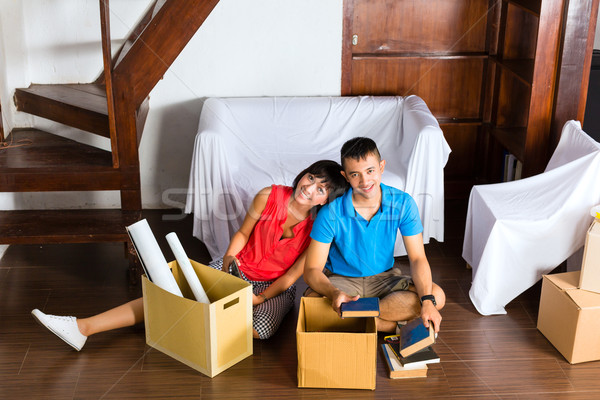 Asian couple having break while moving in Stock photo © Kzenon