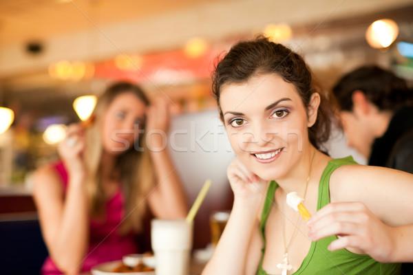 Friends in Restaurant eating fast food Stock photo © Kzenon