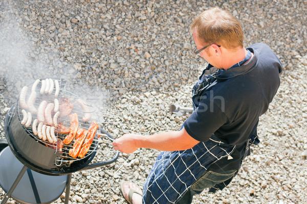 Férfi barbecue grill hús kolbászok kert nyár Stock fotó © Kzenon