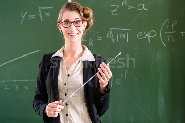 Teacher with pointer in front of a school class Stock photo © Kzenon