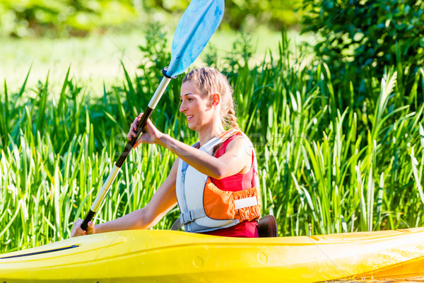 Woman paddling with canoe on forest river Stock photo © Kzenon