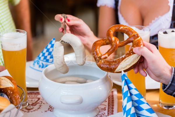 Emberek eszik borjúhús kolbász étterem nő Stock fotó © Kzenon