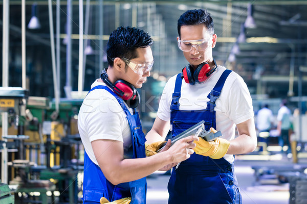 Asian worker checking work piece in production plant Stock photo © Kzenon