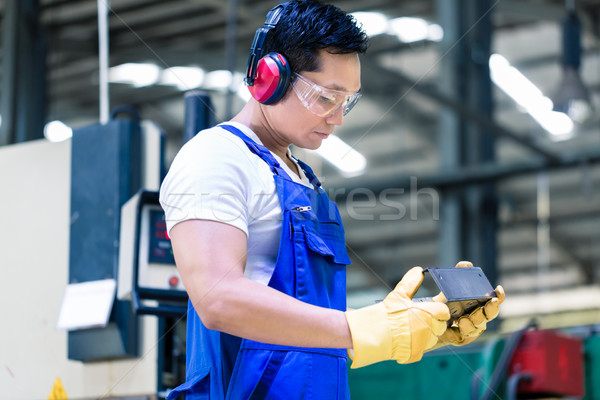 Worker in industrial factory checking work piece Stock photo © Kzenon