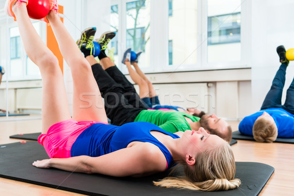 Athletes in health club doing physical exercises on floor with b Stock photo © Kzenon
