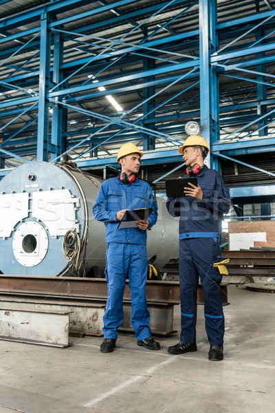 Asian experts checking information during quality control Stock photo © Kzenon