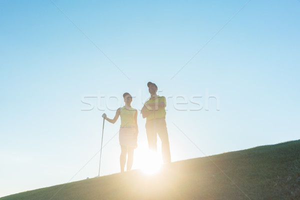Silhouette of a man pointing while standing next to his partner  Stock photo © Kzenon