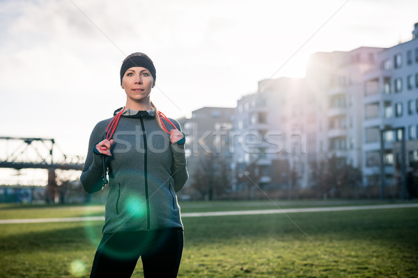 Determined young woman daydreaming while holding a skipping rope Stock photo © Kzenon