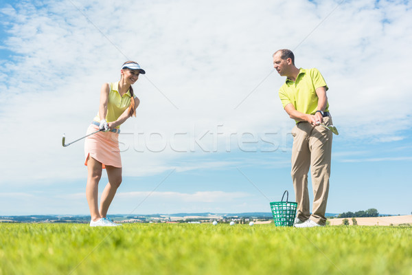 Young woman practicing the correct move during golf class Stock photo © Kzenon