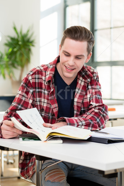 Portrait of a young student smiling while researching information Stock photo © Kzenon