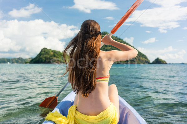 Young woman paddling a canoe on the sea during summer vacation Stock photo © Kzenon