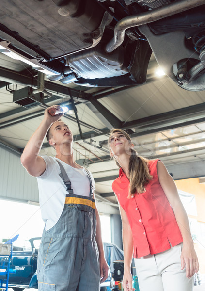 Reliable auto mechanic checking the car of a woman in a modern repair shop Stock photo © Kzenon
