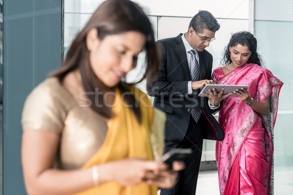 Three Indian business people using modern devices indoors Stock photo © Kzenon