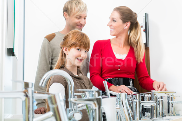 Portrait of a happy family looking for a new bathroom sink faucet Stock photo © Kzenon