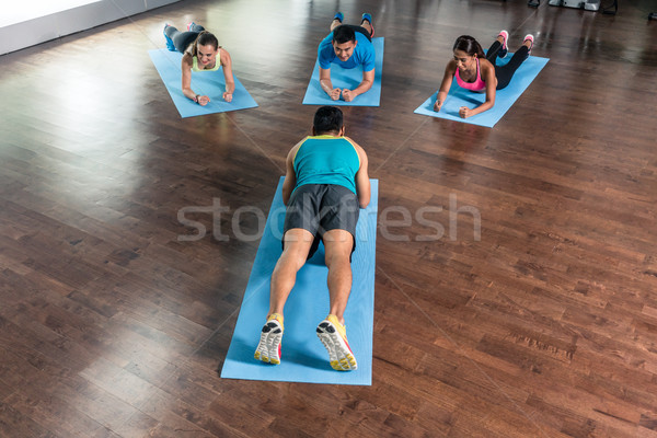 High-angle view of a fitness instructor during group calisthenics class Stock photo © Kzenon