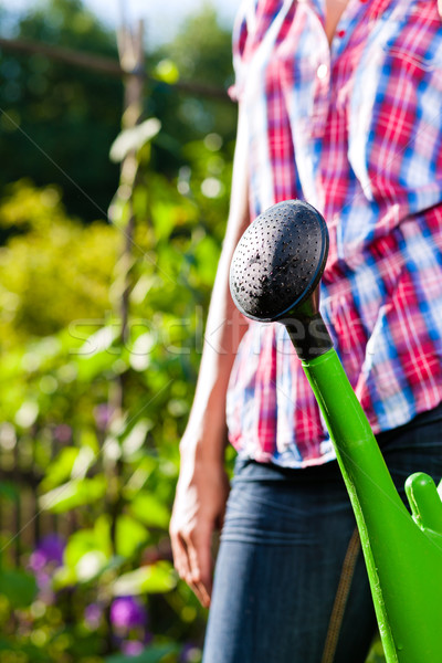Stock photo: Woman in garden with watering can in hand