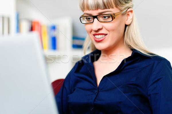 Kadın evden çalışma dizüstü bilgisayar kullanıyorsanız oturma kitaplık çalışma Stok fotoğraf © Kzenon