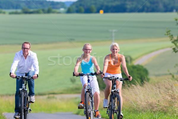 Family having weekend bicycle tour outdoors Stock photo © Kzenon