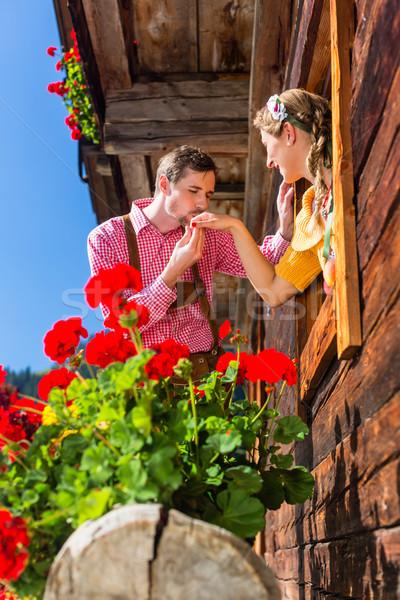Couple in love at mountain hut window Stock photo © Kzenon