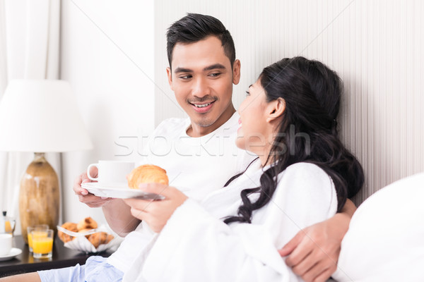 Asian couple lounging in bed at morning Stock photo © Kzenon