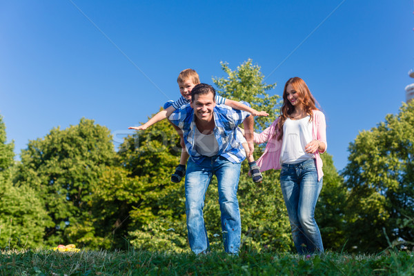Daddy carrying son piggyback on his back  Stock photo © Kzenon