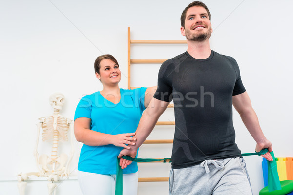 Young man working out with physiotherapist and resistance band Stock photo © Kzenon