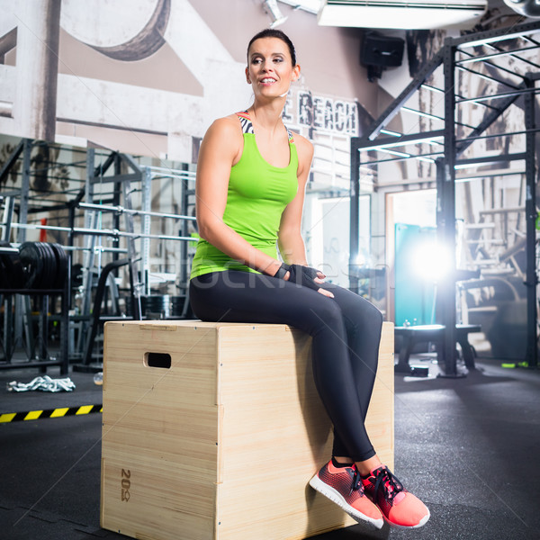 Woman sitting on box in functional training gym Stock photo © Kzenon