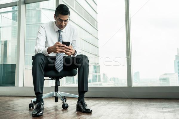 Businessman using a mobile phone while sitting down Stock photo © Kzenon