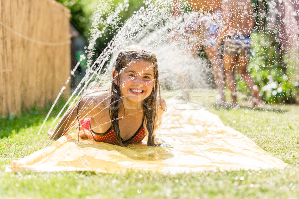 Water fun in garden - girl cooling down with water sprinkler  Stock photo © Kzenon