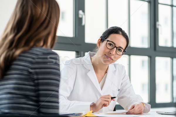 Female physician listening to her patient during consultation in Stock photo © Kzenon